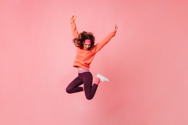 Lovely brunette woman in pink sports headband and tracksuit jumps on isolated pink wall