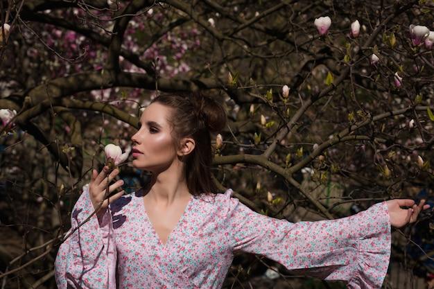 세련된 드레스를 입고 꽃이 만발한 목련 나무 근처에서 포즈를 취하는 사랑스러운 갈색 머리 여자