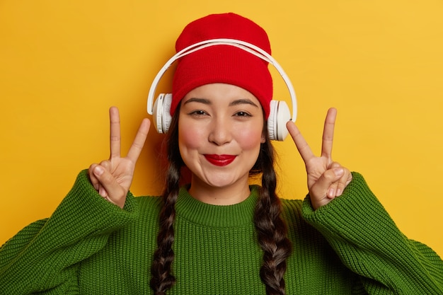 Lovely brunette woman in red hat and green jumper, listens audio track