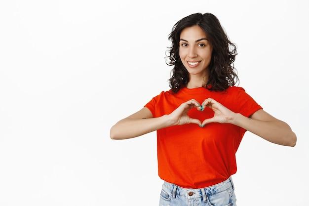 素敵なブルネットの女性はハートのサインを示し、笑顔で心温まるように見え、愛と優しさを表現し、白であなたを好きです