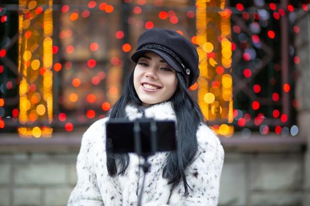 キャップを身に着けている素敵なブルネットの女性、ぼやけた光で通りで自画像を撮る