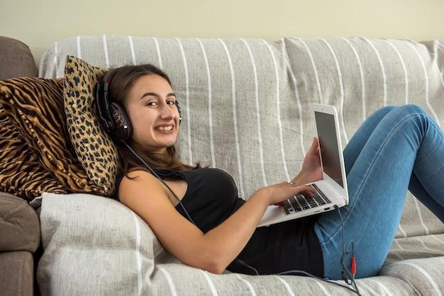 거실에서 소파에 앉아있는 동안 디지털 태블릿을 사용하는 사랑스러운 진정 여자