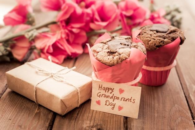 Прекрасная открытка с красными цветами, подарочной коробкой, биркой ремесла и парой кексов.