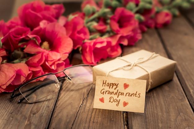 Прекрасная открытка с красными цветами, очками, подарочной коробкой и крафтовой биркой.