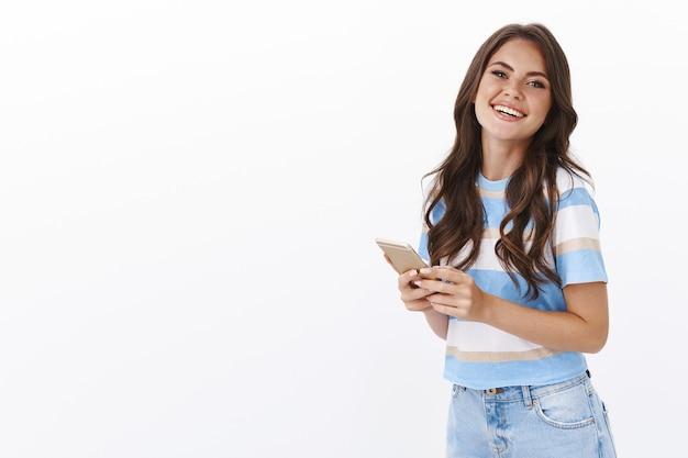 ばかげて笑っている素敵なのんきな魅力の大人の女性、スマートフォンを持って、熱狂的で満足しているカメラを見て、フライトのチケットを予約し、海外で休暇を過ごし、携帯電話アプリを介してホテルに連絡してください