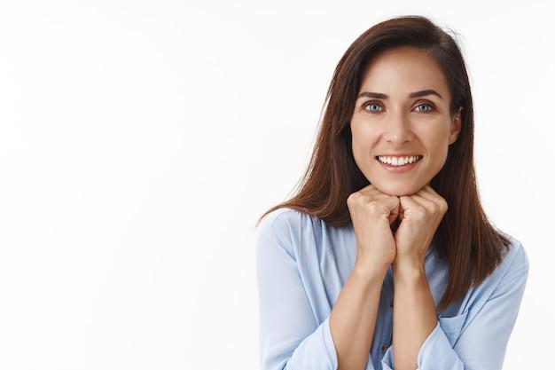 入れ墨のある素敵なのんきな幸運な大人の女性ブルネット、正面で楽しく幸せに見える細い手、面白い話を聞いて、魅了された軽薄な視線、良い会話を楽しんでください、白い壁