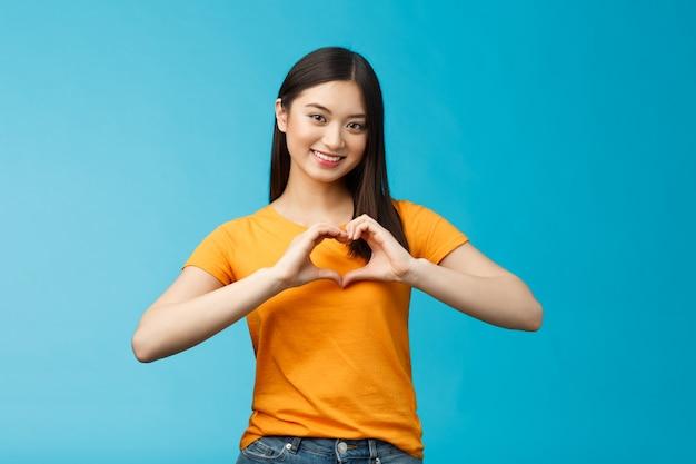 素敵な思いやりのある魅力的なアジアのガールフレンドは、ハートサインを大切にし、関係を大切にし、広く支持的な笑顔を見せ、青い背景に黄色のtシャツを着て、平和と幸福を促進します。