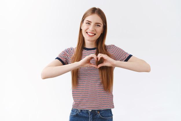 素敵な、思いやりのある若いガールフレンドは、長い金髪のショーのハートのサイン、優しく微笑んでカメラを凝視し、心から愛を告白し、友情とコミットメントを大切にし、白い背景を喜ばせます