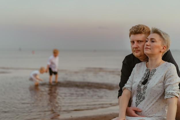 夕焼けの海で遊ぶ妊娠中の妻の子供たちを抱き締める素敵なcaucaisan家族の男