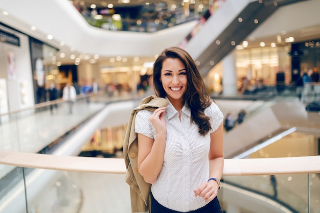 Lovely caucasian brunette with big toothy smile in shirt posing in shopping mall with her beige jacket over the shoulder.