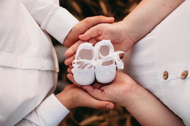 서로 가까이 포즈를 취하는 동안 아기 신발 한 켤레를 들고 사랑스러운 백인 부부