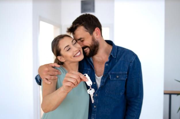 그들의 새 집의 열쇠를 보여주는 포옹에 사랑스러운 백인 부부.