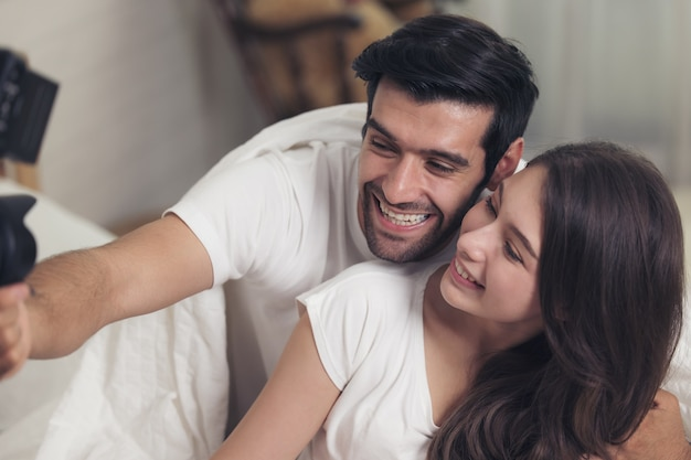 Lovely caucasian couple lying in bed and smile while doing a selfie using a mobile phone