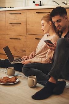 朝食をとりながらラップトップと電話でブラウジング床のキッチンに座っている素敵な白人カップル