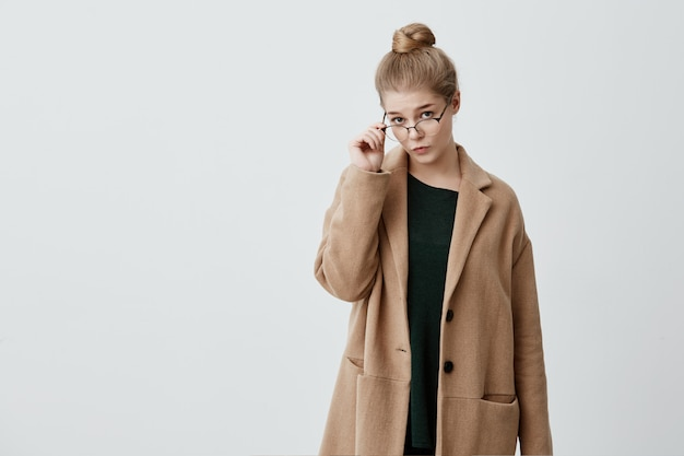 Lovely caucasian female student wears coat, trendy glasses, green sweater, poses with thoughtful and serious expression  as meets her friends and tries to impress them