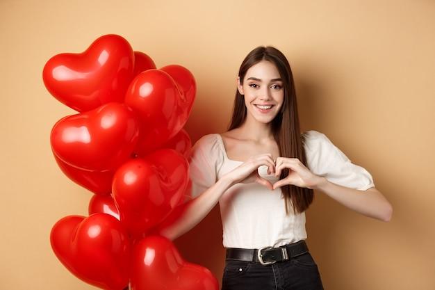 Прекрасная кавказская девушка выражает любовь и нежность, показывая жест сердца и улыбаясь, стоя возле воздушных шаров дня святого валентина, бежевый фон.