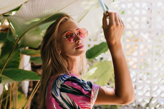 Lovely caucasian girl in pink sunglasses touching green plant.