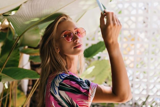 Bella ragazza caucasica in occhiali da sole rosa toccando la pianta verde.