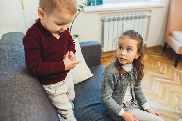 一緒に時間を過ごしながら兄と一緒にソファに座っている素敵な白人の女の子