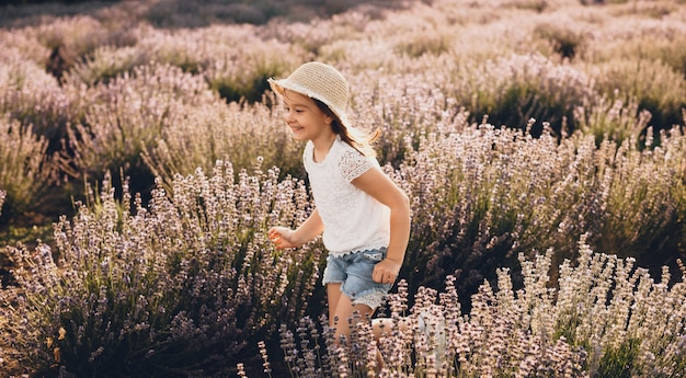 Lovely caucasian girl with white shirt and hat running in a lavender field and smile in a sunny day