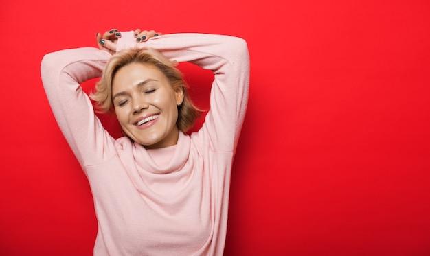 空きスペースのある赤い壁に手を上げてポーズをとる素敵な白人女性