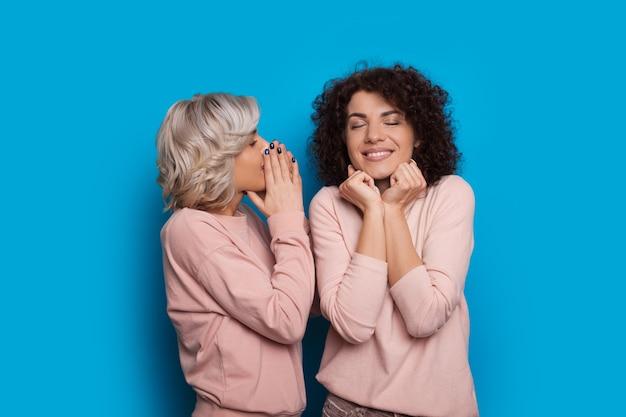 巻き毛の素敵な白人女性は彼女の金髪の友人に耳を傾け、青い背景でポーズをとっている間瞬間を楽しんでいます