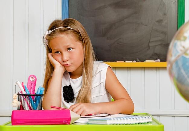 Lovely caucasian school girl bored while doing her homework.