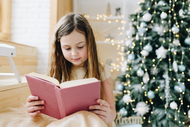 Lovely caucasian schoolgirl reading purple book near decorated christmas tree