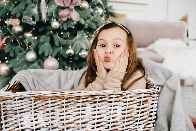 Lovely caucasian schoolgirl sitting in a basket near decorated christmas tree
