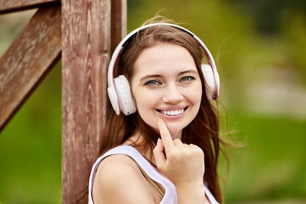 素敵な白人女性がワイヤレスヘッドフォンを使用して屋外で音楽を聴いています