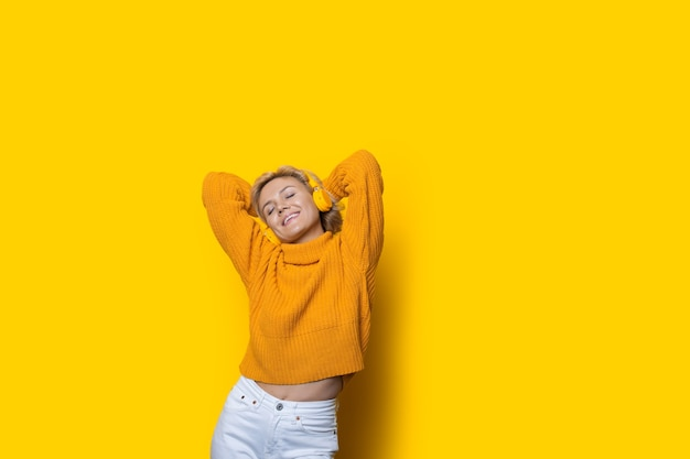 여유 공간이있는 노란색 스튜디오 벽에 이어폰을 통해 음악을 듣고 금발 머리를 가진 사랑스러운 백인 여자