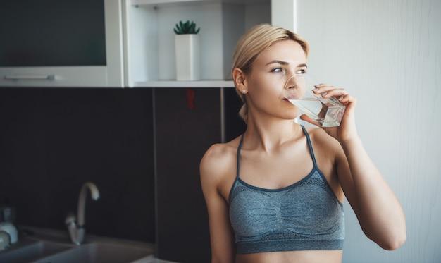 운동복을 입고 금발 머리를 가진 사랑스러운 백인 여자는 집에서 디지털 피트니스 수업 중 물 한 잔을 마시고 있습니다