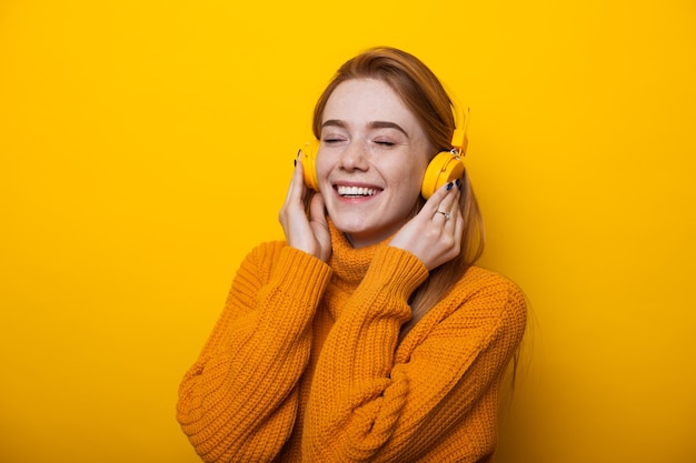 Милая кавказская женщина с рыжими волосами и веснушками слушает музыку в наушниках на желтой стене