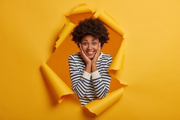 사랑스러운 쾌활한 아프리카 계 미국인 여성이 뺨에 손을 대고 광범위하게 미소 짓습니다.