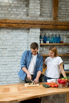 Lovely cheerful couple cooking dinner together and having fun at rustic kitchen