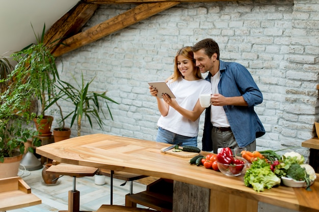 Lovely cheerful couple cooking dinner together, looking recipe at digital tablet  and having fun at rustic kitchen