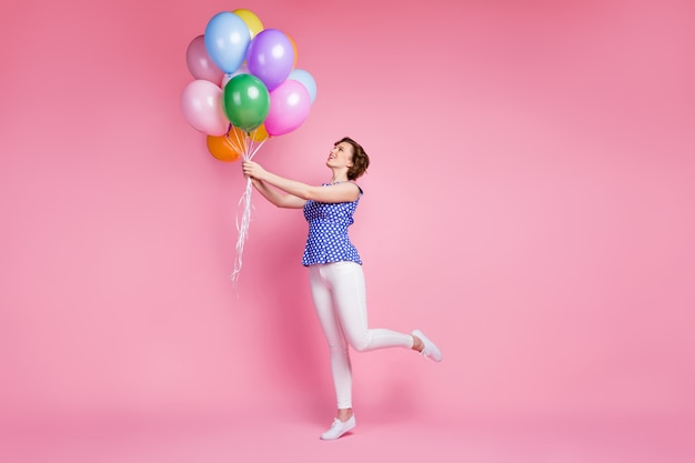 Милая жизнерадостная девушка держит букет воздушных шаров