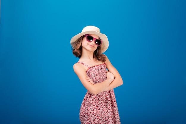 Прекрасная жизнерадостная девушка в шляпе и солнечных очках, стоящая со скрещенными руками на синем фоне