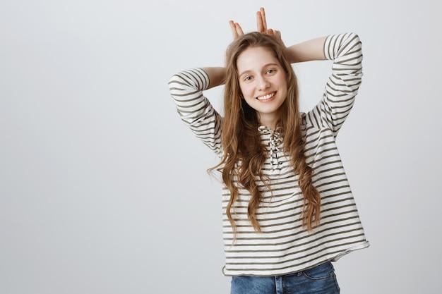 Милая жизнерадостная девушка показывает жест кроличьих ушей и мило улыбается