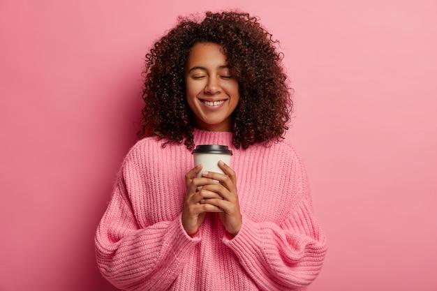 부드러운 미소를 지닌 사랑스러운 쾌활한 밀레 니얼 소녀, 테이크 아웃 커피를 들고 향기로운 카페인 음료와 좋은 맛을 즐깁니다.