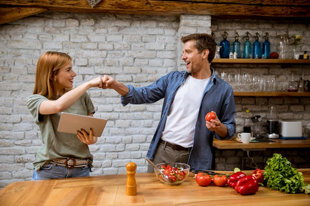 Lovely cheerful young couple cooking dinner together, looking recipe at digital tablet and having fun at rustic kitchen
