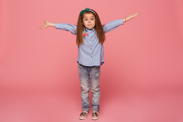 Lovely child girl in hair hoop and casual clothes giving huge hug with open hands while being isolated against pink wall