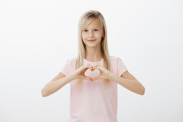 Милый ребенок показывает жест сердца и улыбается