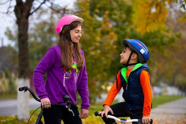 Милые дети, брат и сестра в осеннем парке остановились отдохнуть после велогонки. они отдыхают, улыбаются и смотрят друг на друга.