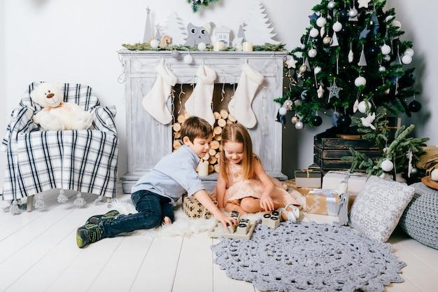 Милые дети, играющие в комнате с елкой и камином. концепция зимних каникул.