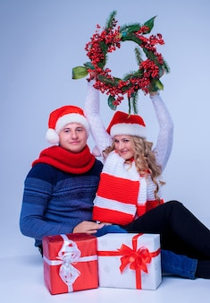 青い背景にプレゼントを保持しているサンタクロースの帽子の素敵なクリスマスのカップル