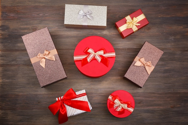 Lovely christmas presents located on wooden board background.