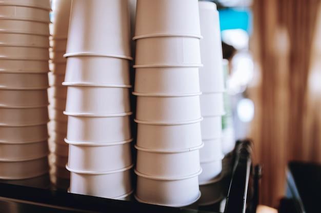 Прекрасные кофейные стаканы стоят на крышке кофемашины в уютной кофейне. .