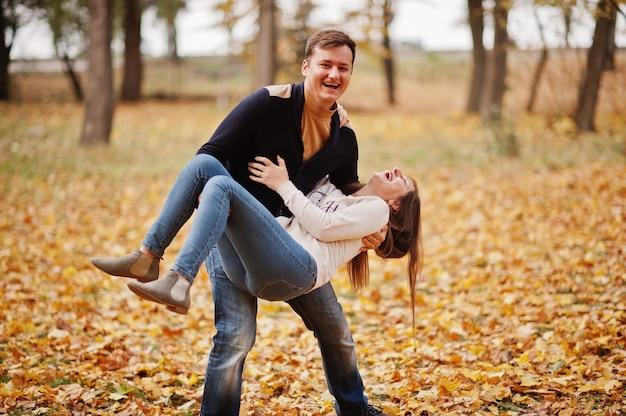 秋の素敵なカップルが公園を去ります。夫は妻を手に持っています。