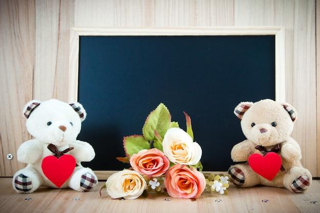 素敵なカップルクマは赤いバラと黒板の床、バレンタインの概念の近くに座る赤いハートを保持します。